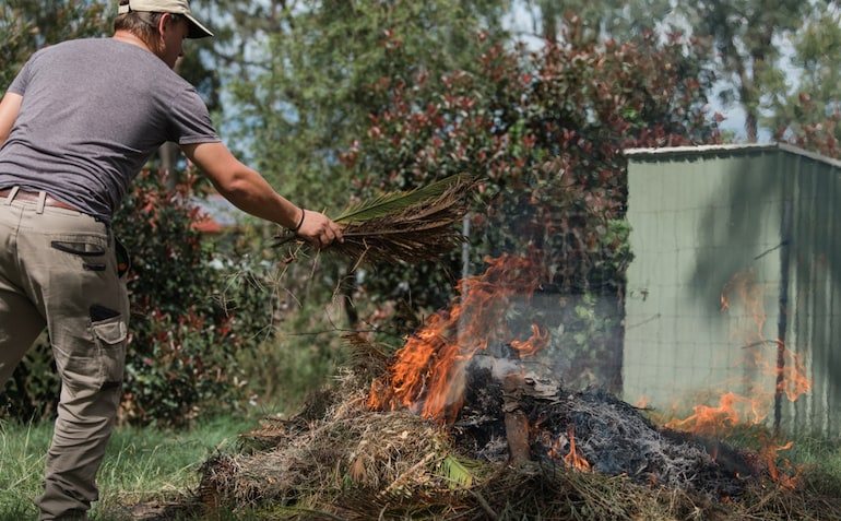 person creating a bonfire out of garden waste