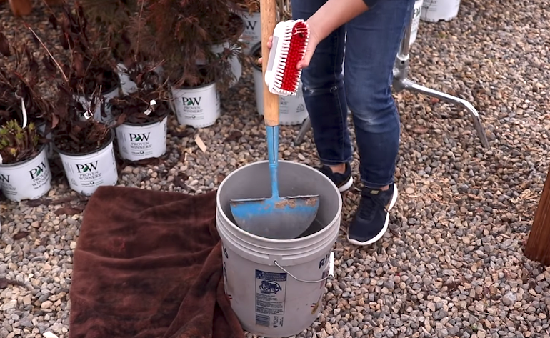 video still of somebody cleaning garden tools in a bucket