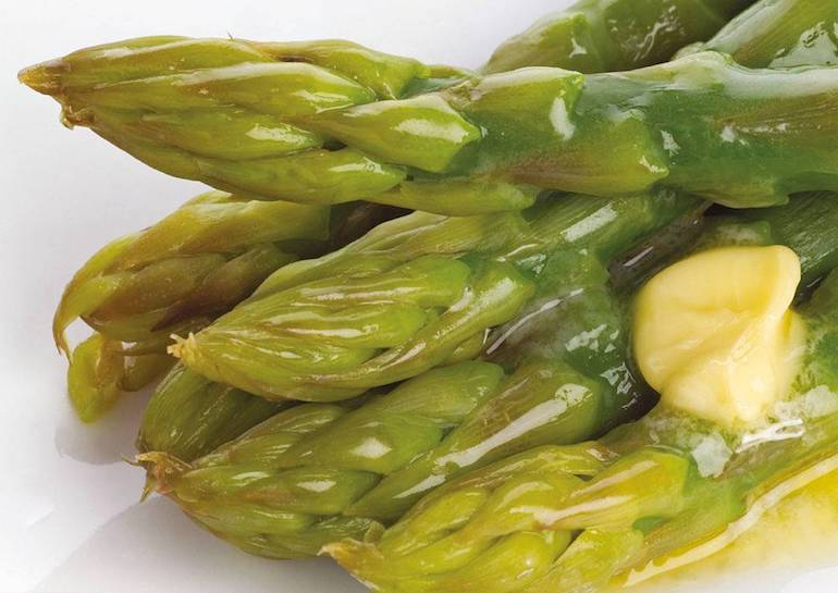 close up of asparagus stalks coated in butter
