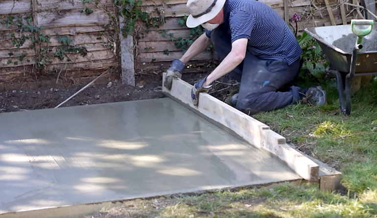 video still of a man smoothing down a wet concrete base for a shed or greenhouse