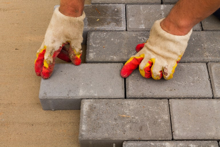 gloved hands laying down paving slabs on sand in courtyard