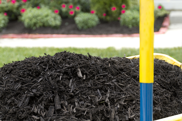 photo of garden mulch with an yellow handle in the foreground