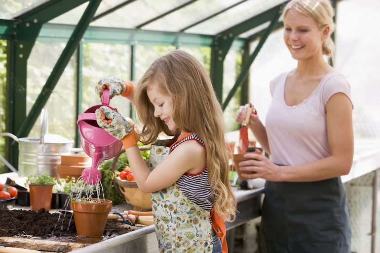 mother and daughter in a greenhouse standing over a workbench