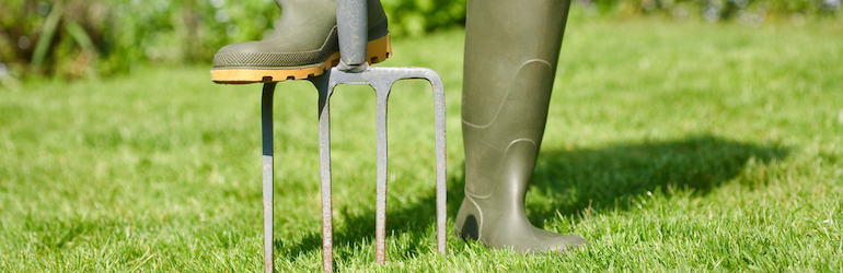 person in green wellies aerating lawn with a garden fork
