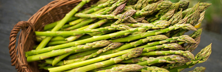 fresh green asparagus in a brown basket