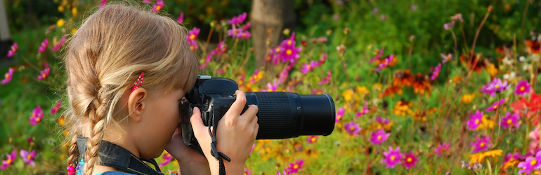 young girl taking photos in a garden