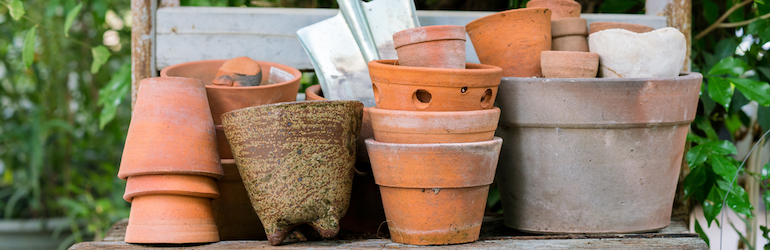 group of terracotta gardening pots and a trowel