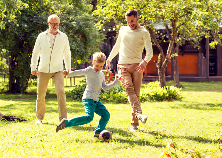 child playing football in the garden with father and grandfather