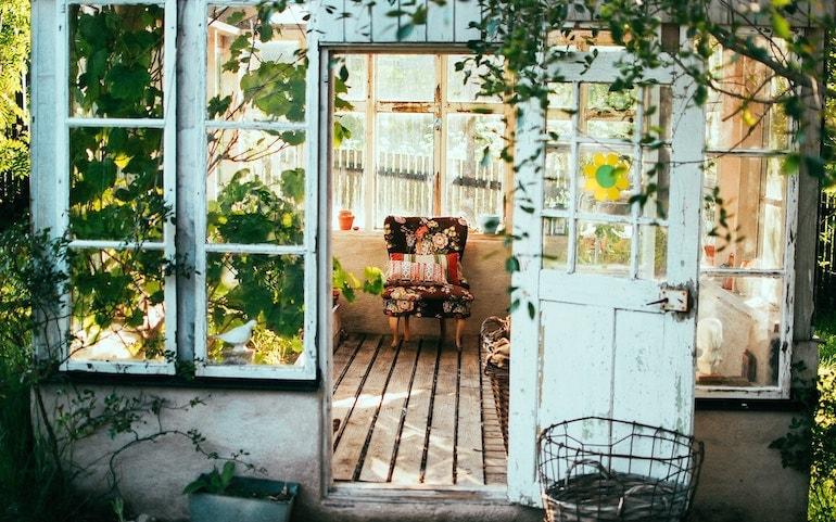blue wooden door leading inside a greenhouse