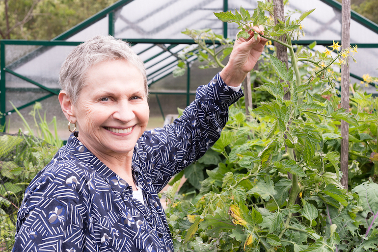 smiling woman standing in front of a greenhouse