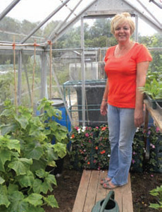 Chris with her row of T&M cucumber plants and infront of her flower pouches full of busy lizzies waiting to hang out